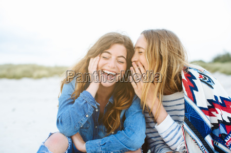 zwei junge weibliche freunde fluestern am